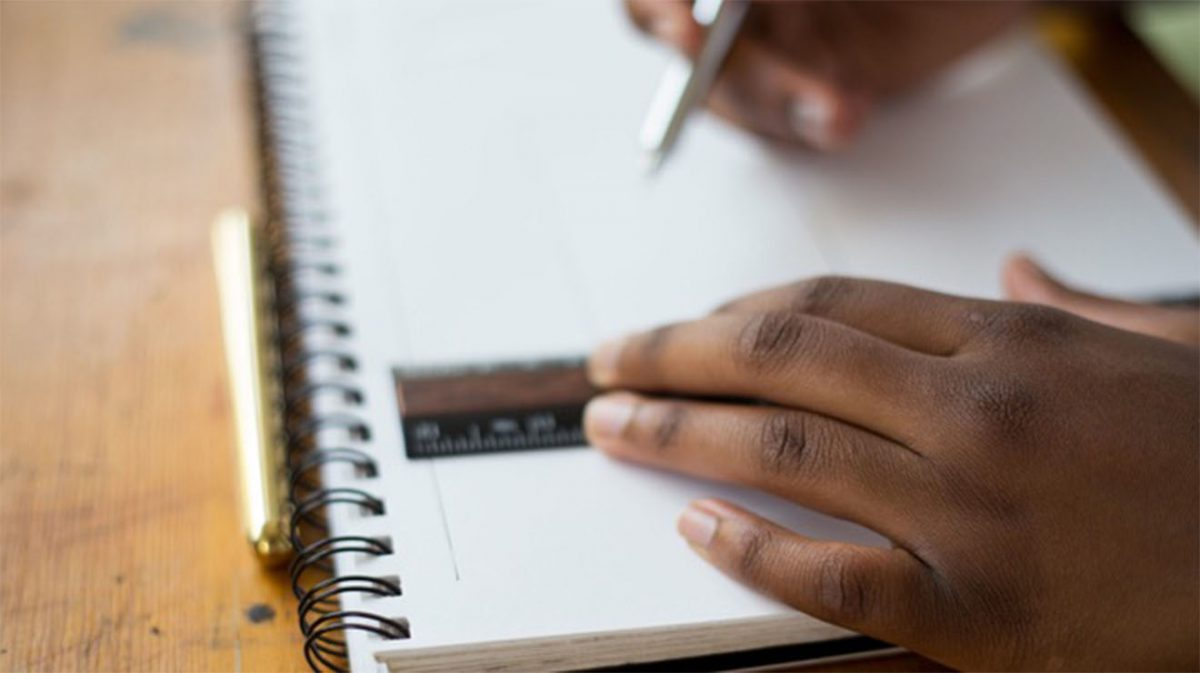 Hands writing in notebook